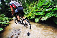 Wetmtb. Young man drive mountain bike over water river Stock Images