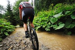 Wetmtb. Young man drive mountain bike over water river Royalty Free Stock Image