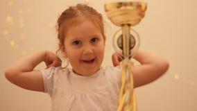 Wettbewerbe und erster Platz belohnung Cup des Siegers Glückliches junges Mädchen, das Taschen auf einem weißen Hintergrund hält  stock video footage