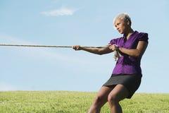 Wettbewerbsfähige Geschäftsfrau, die Tauziehen mit Seil spielt Stockbild