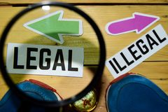 Wettelijk of Onwettig tegenover richtingstekens in het overdrijven met tennisschoenen en kompas op houten stock foto's