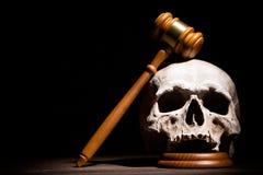 Wettelijk wet, rechtvaardigheid en murdermentconcept De houten hamer van de rechtershamer op menselijke schedel tegen zwarte acht royalty-vrije stock foto