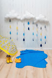 Wettersymbole Handgemachte Raumdekoration bewölkt sich mit Regentropfen, Pfütze, Kindergelben Gummistiefeln, Regenschirm und Ente Stockfotografie
