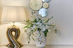 Wewn?trzna izbowa lampowa waza z kwiatami i dekoracyjny lustro na za?wiecamy ?cian? zdjęcie stock