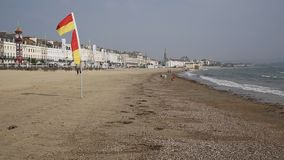 Weymouth beach Dorset UK in late summer popular tourist destination on the south coast. With flag slying in the breeze stock video footage