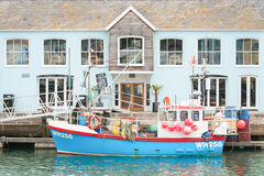 Weymouth Quayside. Weymouth, UK - June 15, 2013: Restaurant building and fishing boat on the picturesque quayside of Weymouth Harbour, UK Stock Photography