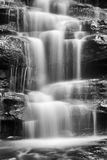 WF Somersby Stream Closest Vert BW. Black white blurred stream of water flowing down the sandstone rocks in Australian central coast rainforest near Gosford Royalty Free Stock Image