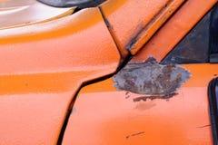 Wgniatający samochód na pomarańczowej powierzchni zdjęcia stock