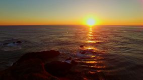 A whale spouts near a rocky bay at sunset stock video