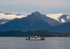 Whale Watching in Alaska. A whale watching boat full of tourists out in the Auke Sound with the mountains in the background royalty free stock photos