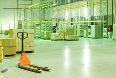 Wharehouse with trolley. Big wharehouse with black trolley and boxes Royalty Free Stock Image