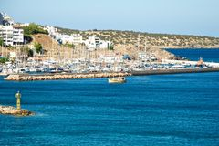 Wharf. On the island of Crete, on the banks of the deep blue sea is a small town. On its pier resting boats and yachts. On all sides the city was surrounded by Stock Photos