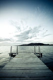 Wharf on a lake. A short dock or wharf on a lake with an island or distant shoreline in the background. Color modified Stock Image