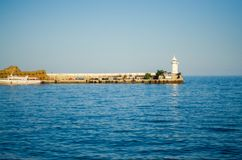 Wharf and lighthouse on the sea. Day nature stock photos