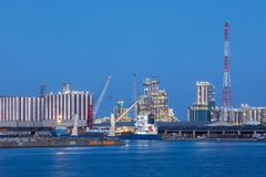 Wharf of petrochemical production plant with moored vessel against a blue sky at twilight, Amtwerp, Belgium. Wharf of petrochemical production plant with moored stock photography