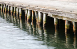 Wharf reflecting in water Stock Photography