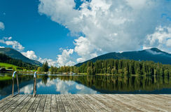 Wharf by the Schwarzsee in Austria. With mirror reflection of the landscape Royalty Free Stock Image