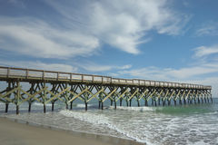 Wharf and wispy clouds. A lovely day at the beach with wispy clouds calm seas and long stretch of wharf Johny Mercer's Pier,  at Wrighstville Beach North Stock Photos