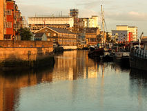 London wharves at sunset. Sunset at wharves on the River at Barking, London showing warehouses, apartment blocks and small boats Royalty Free Stock Photo