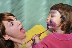 What is it?!. Mother has seen, how its child paints on the face Stock Photography