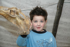 What is this?. Little boy give as questioning look to the camera as he discovers some bones hanging in a indian tent. The tent is a replica and the things Royalty Free Stock Photo