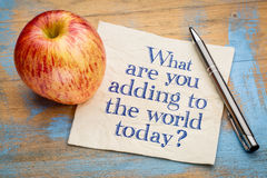 What are adding to the world today?. Handwriting on a napkin with a fresh apple Stock Photos