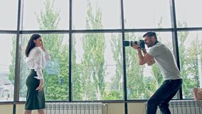 What a beautiful young business woman in a business suit poses for a young photographer on the background of stained stock video