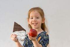 What is better? (focus on the apple). Girl with big chocolate and red apple (focus on the apple Royalty Free Stock Photos