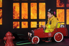 What a Blaze!. A preschool fireman sitting in his vintage firetruck exclaiming about the blaze he sees through nighttime windows Royalty Free Stock Photos