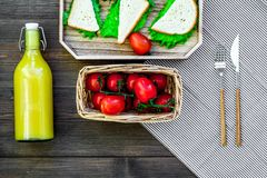 What bring for a picnic. Sanwiches, fruits, vegetables, juice on dark wooden background top view copyspace Royalty Free Stock Photography