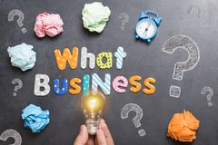What business to start, question on blackboard with colourful letters, crumpled paper and light bulb stock image