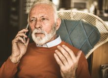 What caused the problem?. Senior business man talking on phone. Close up stock photography