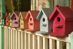 What Color is Your Birdhouse. Colorful collection of birdhouses lined-up on a porch railing Royalty Free Stock Image