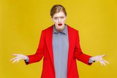 What? Confused ginger red head business woman in red suit. Studio shot, isolated on yellow background Stock Photos