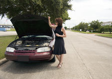 What Could Be Wrong?. A woman standing next to a vehicle apparently experiencing car trouble Royalty Free Stock Photography