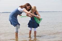 What did we catch. Mother and daughter checking the contents of the fishing net Royalty Free Stock Photos