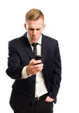 What did they say?. Young handsome businessman using his mobile phone with angry surprised expression Stock Photo