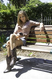 What did he say?. Caucasian female sitting on a bench messaging a friend Royalty Free Stock Photography