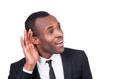 What did you say?. Cheerful young African man in formalwear holding hand near ear and smiling while standing isolated on white background Royalty Free Stock Photography