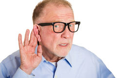 What did you say?. Closeup portrait, senior man, nerd black glasses, hard of hearing, placing hand on ear asking someone to speak up, isolated white background Royalty Free Stock Photo