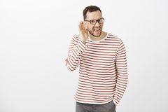 What did you say, repeat. Portrait of annoyed questioned attractive european guy in black glasses, asking question and. Holding hand near ear, hearing nothing Stock Images
