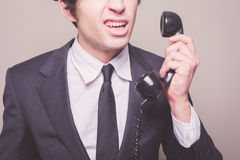 What did you say?. Young businessman can't believe what he is hearing on the phone Royalty Free Stock Photography