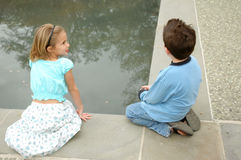 What did you wish for?. Little girl gives a questioning glance over to a little boy as they stare into the wishing pond Royalty Free Stock Images