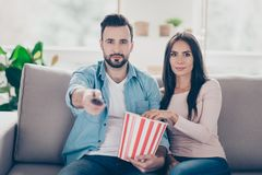 So what do we have today on TV? Cute cheerful carefree beautiful. Kind lovely wife and husband spend time together by watching tv Stock Photos