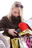 What do I have left?. Cute teenage girl checking the content of her wallet surrounded by shopping bags Stock Images