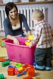 What do you have here?. Young woman with baby boy during plaing. Woman showing toy to baby. They are at container with toys. Baby standing back to camera. Front royalty free stock images