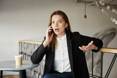 What do you mean deal is canceled. Portrait of expressive attractive urban woman in stylish clothes sitting in cafe. Leaning on handrail, drinking coffe royalty free stock photo