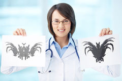What do you see?. Smiling psychiatrist showing two different pictures Royalty Free Stock Photo