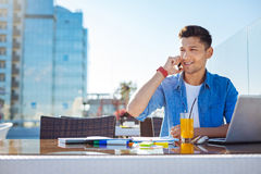 Young freelancer having business call outdoors. What do you think about this. Self employed guy looking into vacancy while drinking a fresh juice and discussing Royalty Free Stock Image