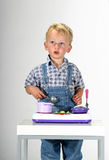 What do you want for breakfast?. Cute blond toddler boy cooking in his toy kitchen royalty free stock image